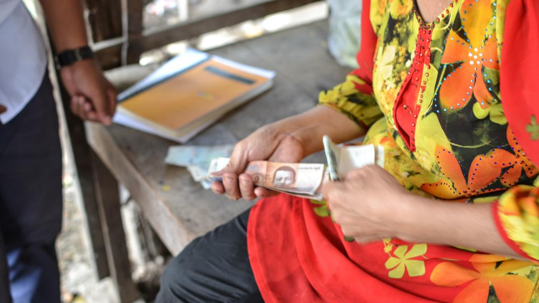Micro-finance beneficiary pays back her loan in Cambodia.